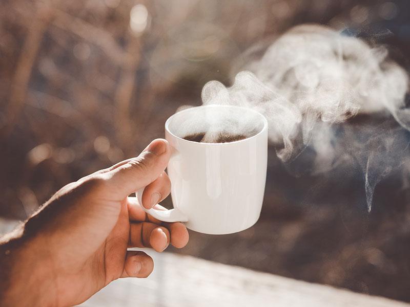 hand holding a white mug of hot coffee