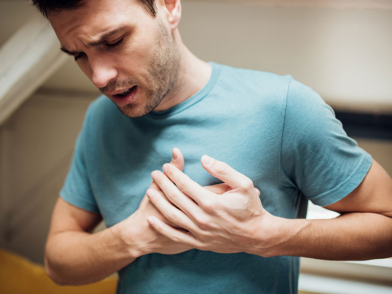 Man in pain with hands on his chest