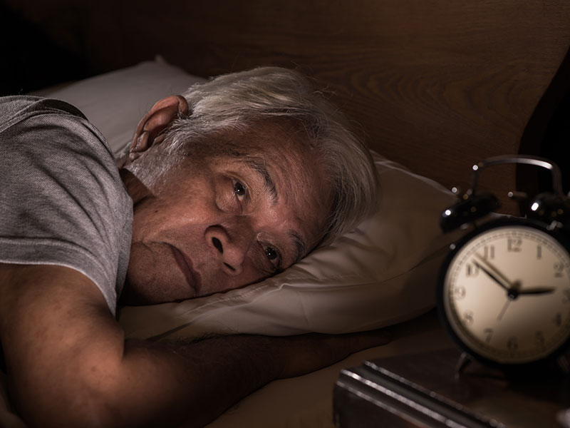 Older man looking at clock in bed