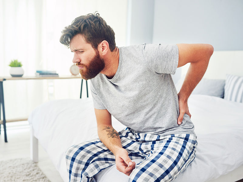 Man sitting on bed holding his lower back