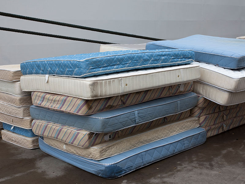 Pile of old mattresses outside