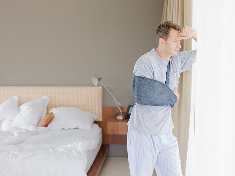 Man with arm in sling in bedroom