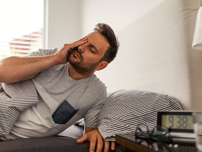 Man waking up in bed with hand covering one eye
