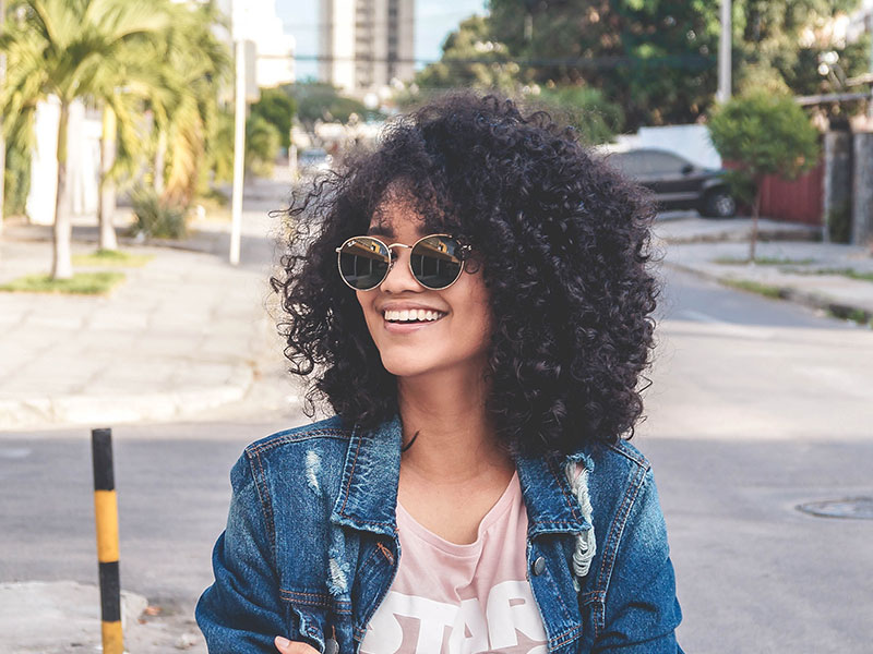 Woman with dark curly hair wearing sunglasses