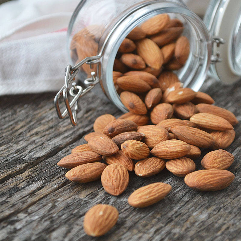 Almonds on table coming out of jar