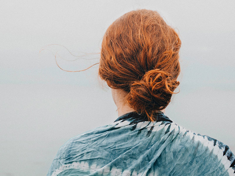 Woman with red curly hair tied in a bun