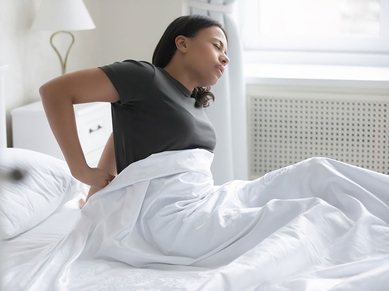 African woman wakeup sitting on bed feels low back pain