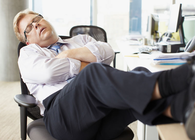 Businessman sleeping with feet up at desk