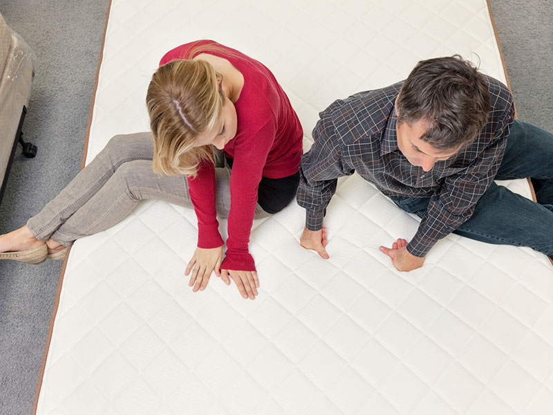 Couple sitting on mattress in store