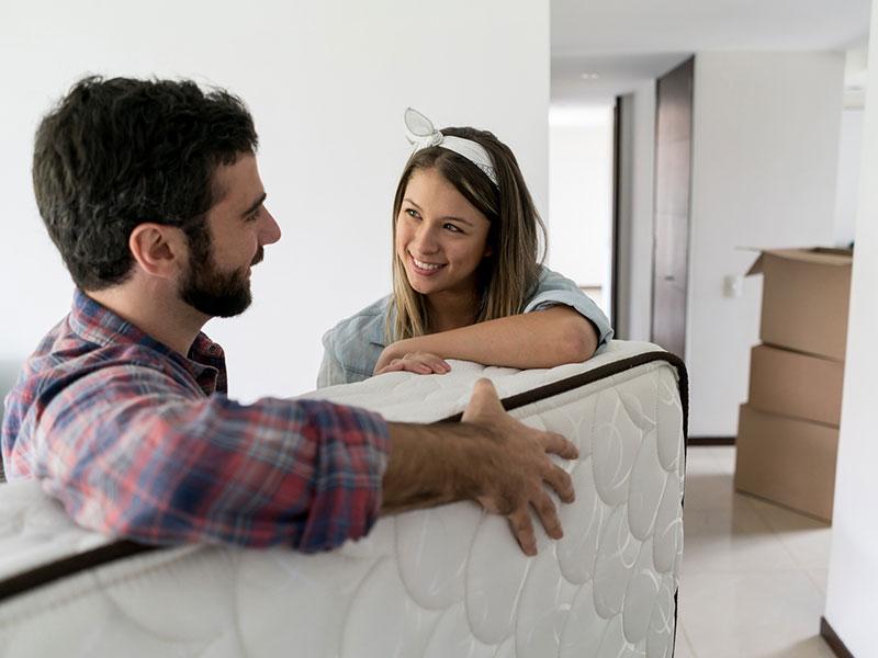 Happy couple moving a mattress