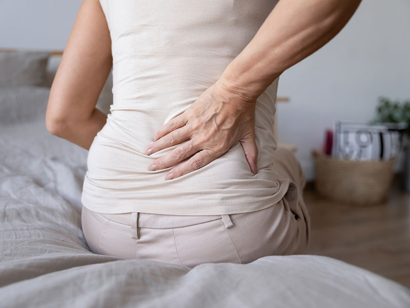 mature woman sit on bed touch back feel backpain