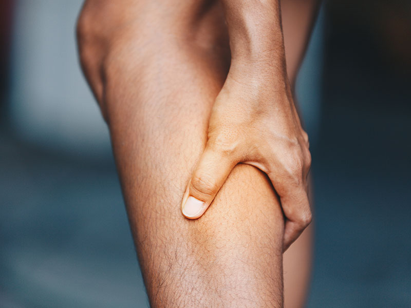 hand holding lower leg in pain