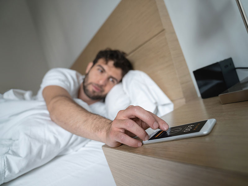 man waking up to alarm on his smartphone