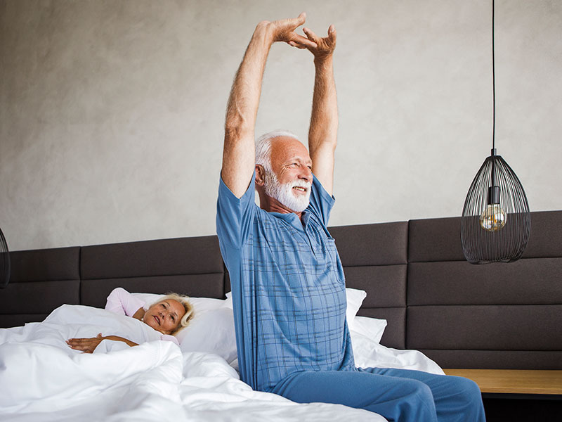 older man stretching in bed