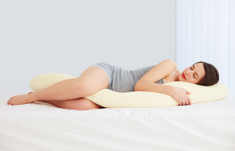 pregnant woman sleeps comfortable with tummy supporting pillow