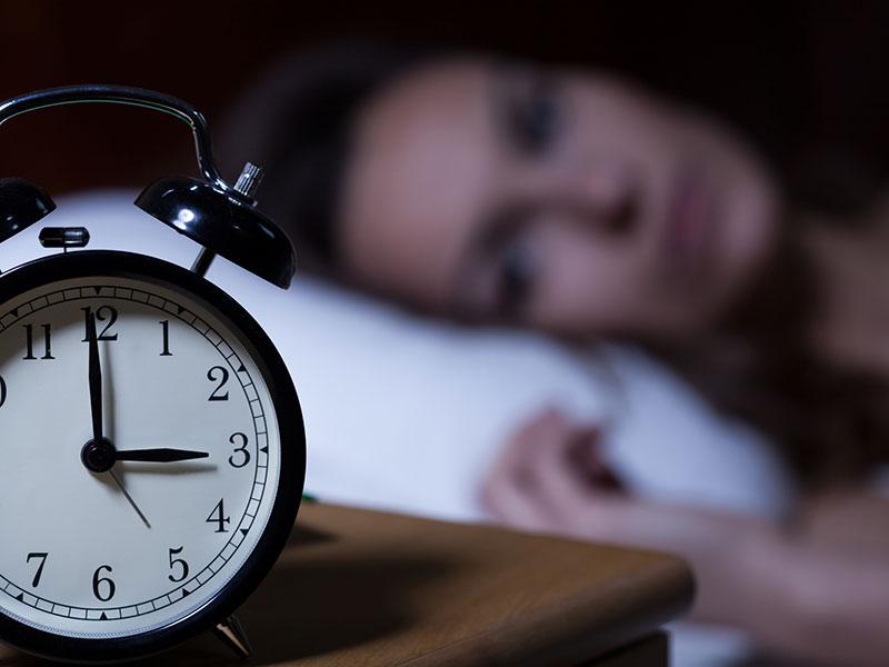 woman in bed looking at alarm clock at 3am