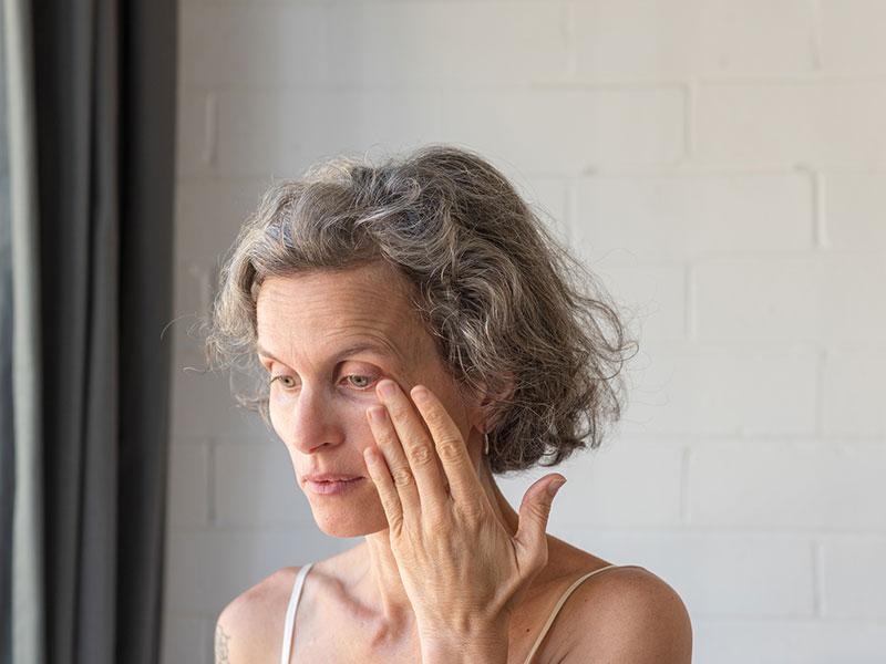 woman rubbing left eye