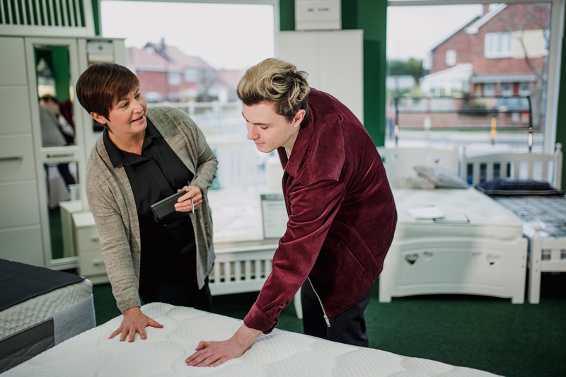 A saleswoman is assisting a young man as he shops for a new mattress