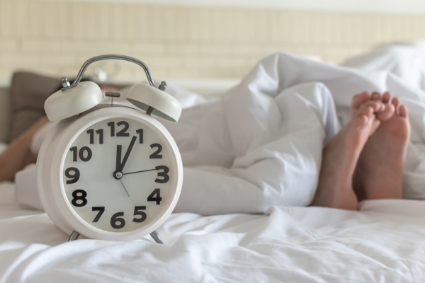 Alarm clock at foot of bed with bare feet showing