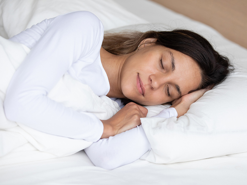 Calm attractive young girl sleeping in bed