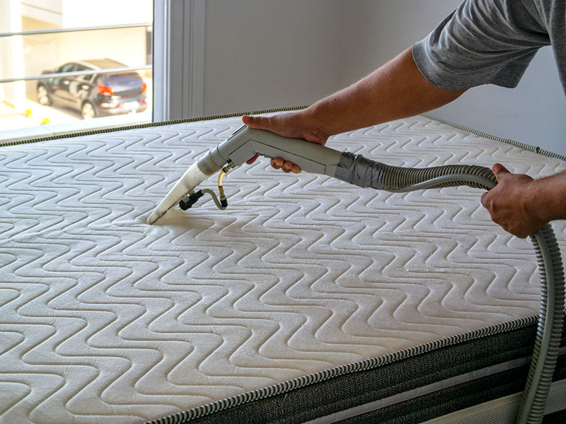 a person cleaning a mattress