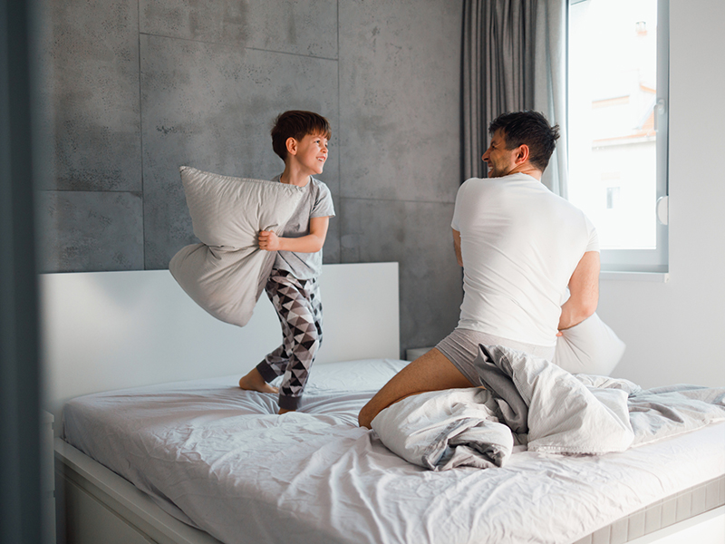 father and his 7 years old son are having a pillow fight in the bed