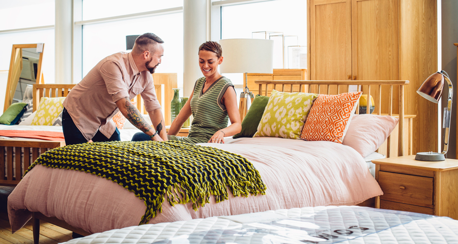 A middle aged couple are shopping in a furniture store for a new bedroom