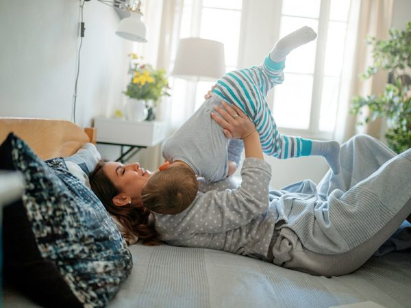 Happy mother playing with her toddler lying in bed