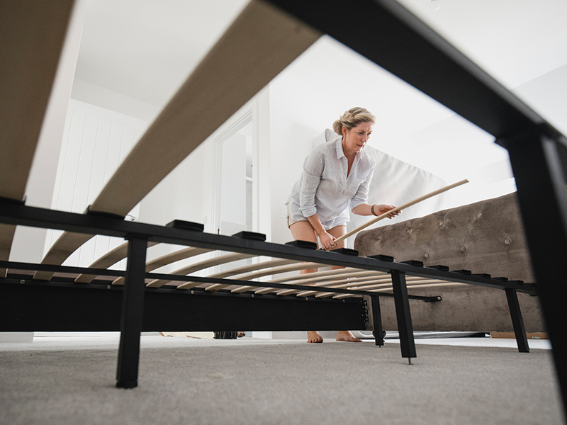 Low angle view of a mature woman setting up her bed in her new home.