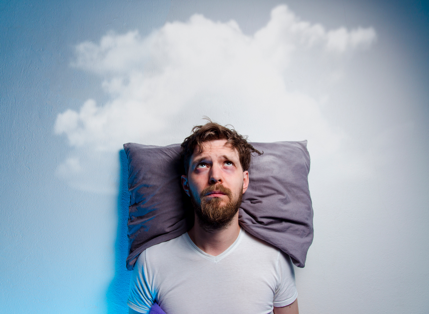Man having insomnia laying in bed on pillow, looking up to gray cloud over his head