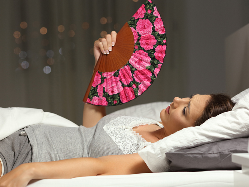 Overwhelmed woman fanning suffering heat stroke