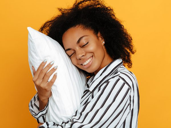 Sleeping. Dreams. Woman portrait. Afro American girl in pajama is hugging a pillow and smiling, on a yellow background