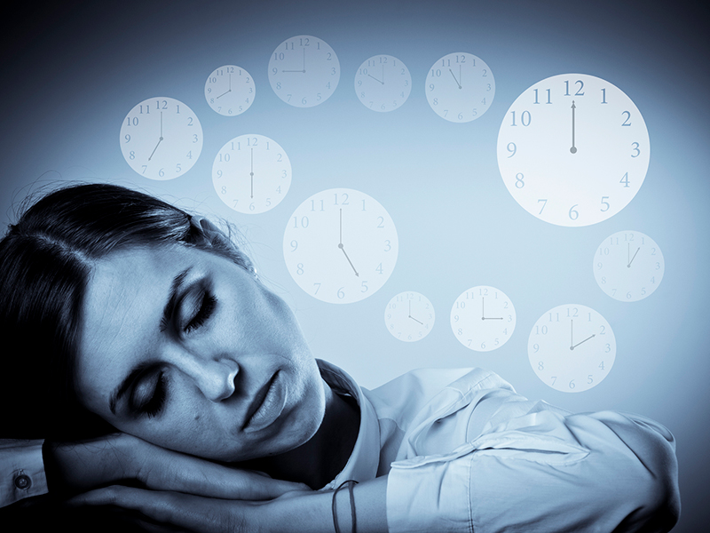 Tired young woman in white is sleeping. Sleep and Time concept. Clocks as background