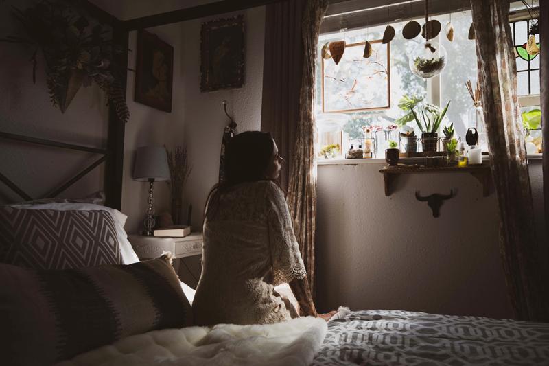 Woman sitting in pleasant bedroom