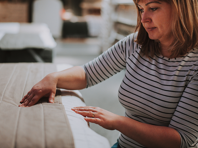 Young woman examining orthopaedic mattress in the shop