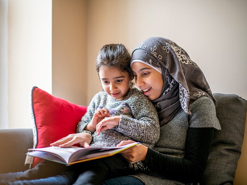 girl wearing a hijab sits on a couch with her little sister on her lap and reads her a bedtime story