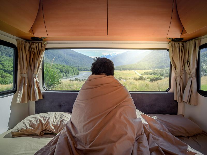 man looking at mountain scenery through the window in camper van