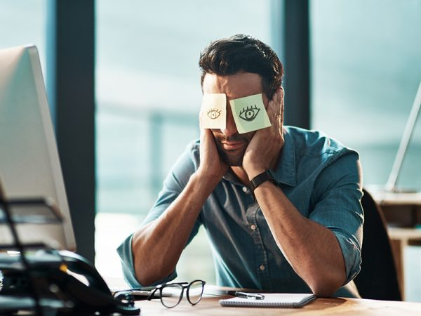 tired young businessman working at his desk with adhesive notes covering his eyes