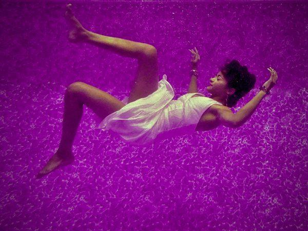 woman floating in purple space