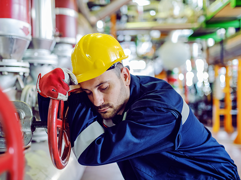 Hardworking caucasian worker in working clothes leaning on big valve and sleeping