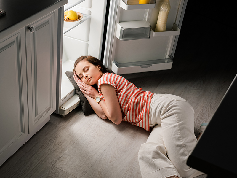 High angle view of attractive girl sleeping on pillow near open refrigerator