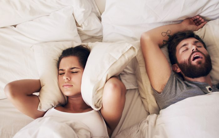 Shot of a young woman covering her ears with a pillow while her husband snores